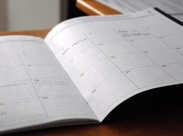 手帳を開いてスケジュールを確認する